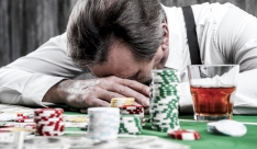 It is not my day. Depressed senior man in shirt and suspenders leaning his head at the poker table with money and gambling chips laying all around him